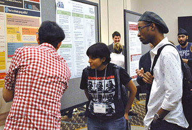 Three CHIIR participants discuss a poster