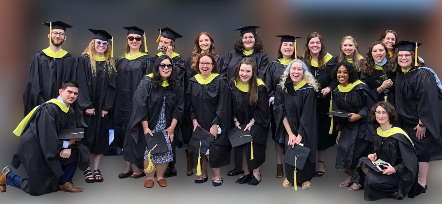 19 SILS graduates wearing black robes and yellow hoods.
