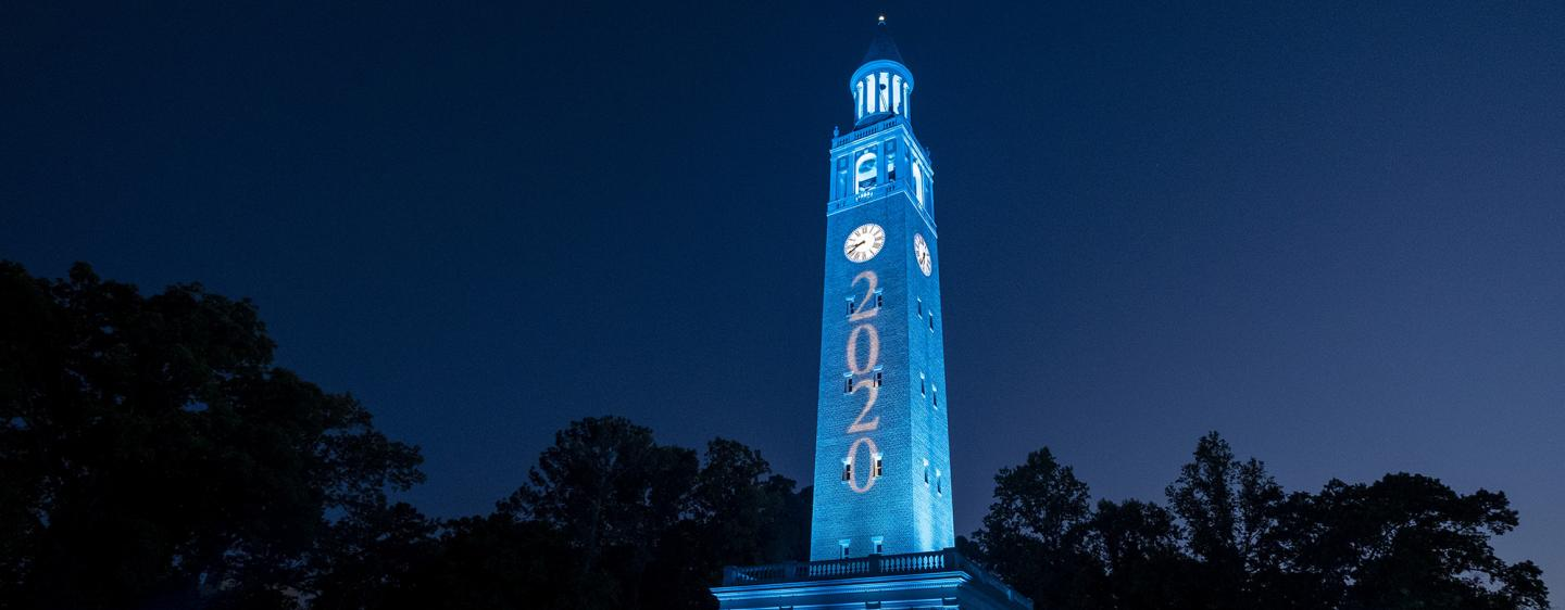 Morehead-Patterson Bell Tower at night, illuminated in blue with 2020 on the side.